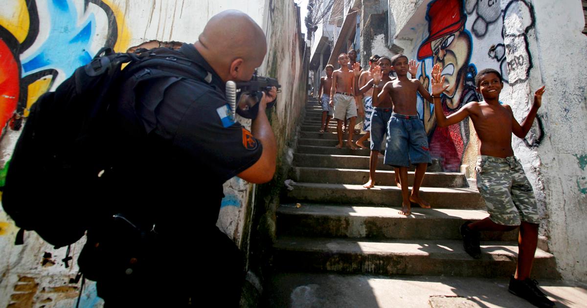 Policial aponta sua arma contra crianças na Favela do Jacarezinho